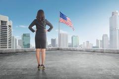 Bakre sikt av affärskvinnan som överst ser amerikanska flaggan av th Royaltyfria Foton