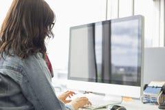 Bakre sikt av affärskvinnan som använder den skrivbords- datoren i idérikt kontor royaltyfri fotografi