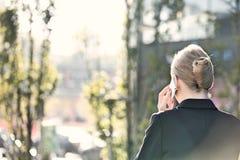 Bakre sikt av affärskvinnan som använder mobiltelefonen på solig dag arkivfoto