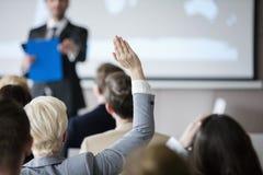 Bakre sikt av affärskvinnan som lyfter handen under seminarium Royaltyfria Bilder