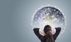 Bakre sikt av affärskvinnan som ser jätte- jordkommunikation för nätverk Arkivfoto
