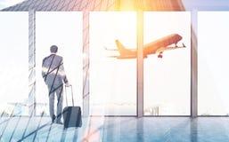 Bakre sikt av affärsmannen i flygplats arkivfoto