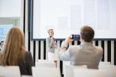 Bakre sikt av affärsmannen som fotograferar den kvinnliga offentliga högtalaren i seminariumkorridor Fotografering för Bildbyråer