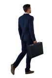 Bakre sikt av affärsmannen som går med portföljen arkivbild