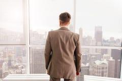Bakre sikt av affärsmannen som står det near fönstret royaltyfria foton