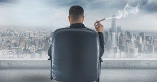 Bakre sikt av affärsmansammanträde på stol och att se staden, medan röka cigarren Arkivbild