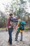Bakre sikt av att fotvandra par med ryggsäckar som går i skog Fotografering för Bildbyråer