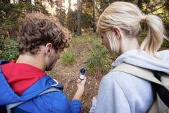 Bakre sikt av att fotvandra par som kontrollerar kompasset Royaltyfria Foton