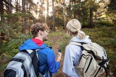 Bakre sikt av att fotvandra par som rymmer en kompass och framåtriktat pekar Royaltyfri Bild