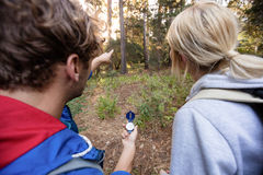 Bakre sikt av att fotvandra par som rymmer en kompass och framåtriktat pekar Arkivbild
