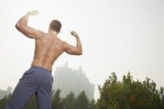 Bakre sikt av barn, muskulös man med ingen skjorta på att böja hans tillbaka muskler, utomhus i Peking, Kina, med en kameralutande Royaltyfria Foton