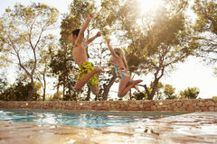 Bakre sikt av barn på semesterbanhoppning in i utomhus- pöl fotografering för bildbyråer
