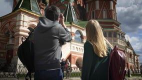 Bakre sikt av barnparturister som tar bilder av Moskvadomkyrkan, Kreml lager videofilmer