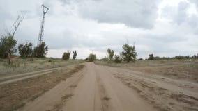 Bakre sikt av bilkörning längs en lantlig grusväg stock video