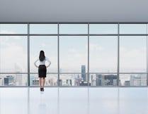 Bakre sikt av brunettkvinnan i kontoret som ser till och med fönstret Royaltyfria Bilder