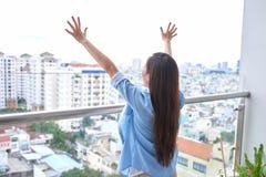 Bakre sikt av den aktiva sportiga kvinnan som str?cker p? balkong arkivbilder