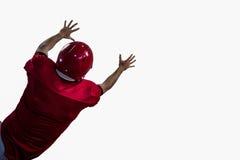 Bakre sikt av den amerikanska fotbollsspelaren som försöker att fånga fotboll Royaltyfri Bild