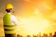Bakre sikt av den asiatiska arbetarmannen, i säkerhetsväst, handskar, anseende för gul hjälm och för skyddande maskering och att  arkivfoto