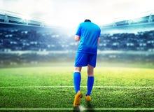 Bakre sikt av den asiatiska fotbollsspelaremannen att fira hans m?l royaltyfri fotografi