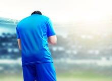 Bakre sikt av den asiatiska fotbollsspelaremannen att fira hans m?l arkivbilder