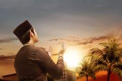 Bakre sikt av den asiatiska muslim mannen som står och ber medan lyftta händer med den härliga moskén royaltyfria foton