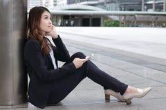 Bakre sikt av den attraktiva unga asiatiska affärskvinnan i formell kläder som sitter på golv och tänker om hennes jobb på stads- royaltyfria bilder