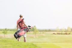 Bakre sikt av den bärande golfklubbpåsen för man, medan gå på kursen Royaltyfria Foton