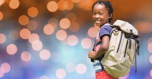 Bakre sikt av den bärande ryggsäcken för skolbarn över bokeh Royaltyfri Fotografi