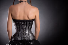 Bakre sikt av den gotiska flickan i silverläderkorsett Royaltyfri Foto
