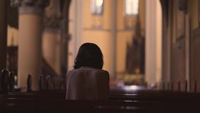 Bakre sikt av den kristna kvinnan som ber till GUDEN