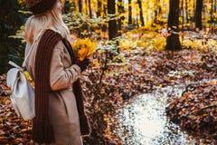 Bakre sikt av den kvinnliga hållande buketten av gula höstlönnlöv i hennes behandskade händer Jordning som täckas med orange sido royaltyfria bilder