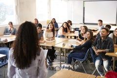 Bakre sikt av den kvinnliga högstadiumläraren Standing At Front Of Class Teaching Lesson royaltyfria foton