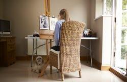 Bakre sikt av den kvinnliga tonårs- bilden för konstnärSitting At Easel teckning av hunden från fotografiet i kol royaltyfri fotografi