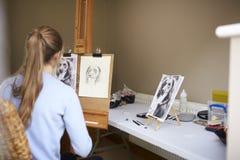 Bakre sikt av den kvinnliga tonårs- bilden för konstnärSitting At Easel teckning av hunden från fotografiet i kol royaltyfria foton