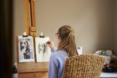 Bakre sikt av den kvinnliga tonårs- bilden för konstnärSitting At Easel teckning av hunden från fotografiet i kol royaltyfria bilder
