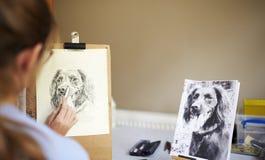 Bakre sikt av den kvinnliga tonårs- bilden för konstnärSitting At Easel teckning av hunden från fotografiet i kol arkivbilder