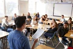 Bakre sikt av den manliga högstadiumläraren Standing At Front Of Class Teaching Lesson royaltyfria bilder