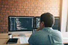 Bakre sikt av den moderna koden för websitebärarehandstil för program och att se bildskärmskärmen med analysering av kod arkivfoto