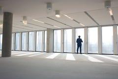 Bakre sikt av den mogna affärsmannen som besöker tomt kontorsutrymme royaltyfri bild
