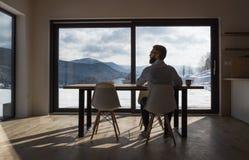 Bakre sikt av den mogna mannen som sitter p? tabellen i nytt hem, genom att anv?nda minnestavlan royaltyfri fotografi