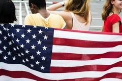 Bakre sikt av den olika kvinnagruppen med den amerikanska nationflaggan royaltyfri foto