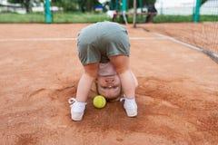 Bakre sikt av den roliga lilla flickan med tennisbollen på tennisbanan Fotografering för Bildbyråer
