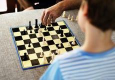 Bakre sikt av den unga caucasian pojken med schackboardgame Royaltyfri Bild