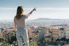 Bakre sikt av den unga kvinnan som bär i avrivet t-skjorta anseende på hög poäng och ser cityscape Royaltyfri Fotografi