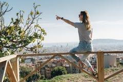 Bakre sikt av den unga kvinnan som bär i avrivet t-skjorta sammanträde på hög poäng och ser cityscape Royaltyfri Fotografi