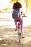 Bakre sikt av den unga kvinnan som cyklar längs gatan för att arbeta Arkivfoto