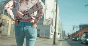 Bakre sikt av den unga kvinnan som går i stadsgatorna Royaltyfri Bild