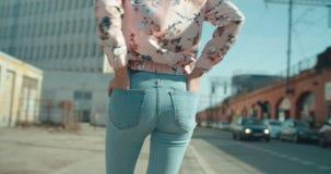 Bakre sikt av den unga kvinnan som går i stadsgatorna Fotografering för Bildbyråer
