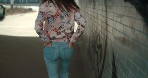Bakre sikt av den unga kvinnan som går på stadsgator Royaltyfria Bilder