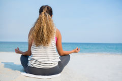 Bakre sikt av den unga kvinnan som mediterar på sand på stranden Arkivbild